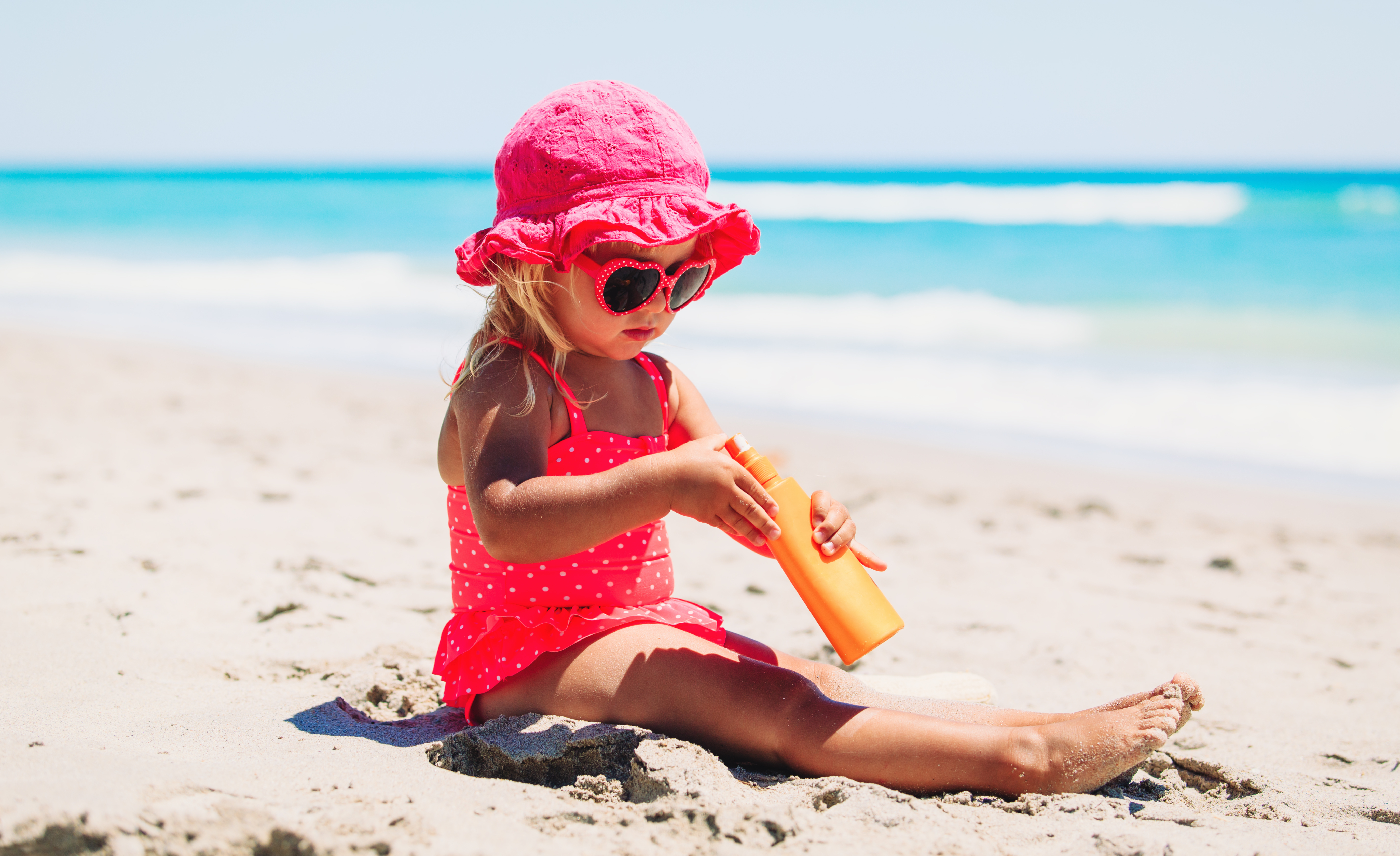 sun protection concept little girl with suncream at beach shutterstock 557242537
